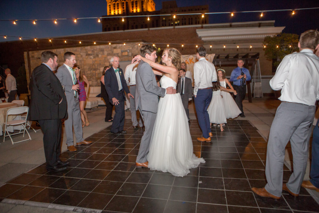 Wedding couple dancing under the stars on an outdoor terrace to wedding dj music